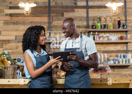 Smiling waiter and waitress using digital tablet at counter in cafe - Stock Photo