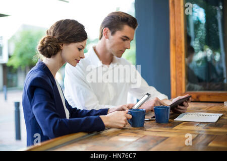 Businessman and woman using mobile phone and digital tablet at counter in cafe - Stock Photo