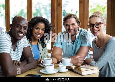 Portrait smiling friends with coffee cups on table in café - Stock Photo