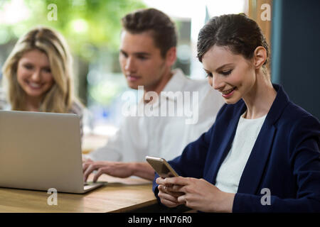 Young woman using mobile phone in café - Stock Photo