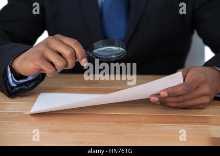 Mid section of businessman looking at document through magnifying glass - Stock Photo