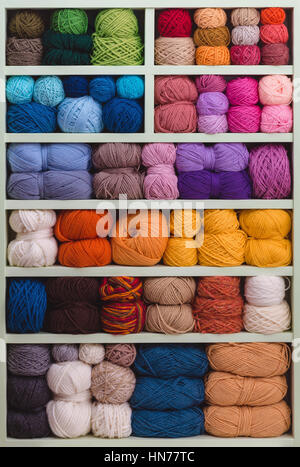 Colorful Balls Of Wool On Shelves. Variety of knitting yarns. Different Yarn balls in multiple colors. Yarn Storage. - Stock Photo