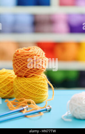 Knitting yarn and needles on blue table against blurred background. Close up of multi colored woolen balls. - Stock Photo