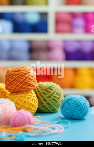 Knitting yarn on blue table against blurred background. Close up of multi colored woolen balls. - Stock Photo