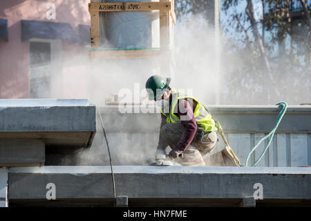 Laguna Beach, California. Construction worker sanding the roof flat on a new lifeguard station. - Stock Photo