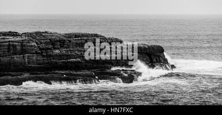 Ocean waves breaking on rugged coastal cliffs. Black and white landscape - Stock Photo