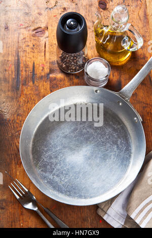 an empty pan on a wooden table. salt, pepper, olive oil. space for writing the text, recipes, advertising or menu - Stock Photo