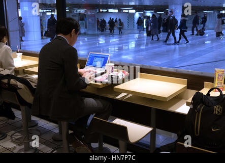 Japanese businessman, Asian manager working with laptop computer at McDonald's fast food restaurant in train station, - Stock Photo