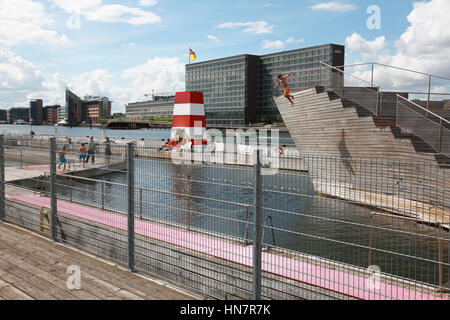 A boy jumping from the diving tower at the Islands Brygge  outdoor swimming pool in Copenhagen harbour, Denmark - Stock Photo