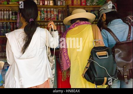 Female tourists in souvenir shop, Lugu Lake, Yunnan, China - Stock Photo