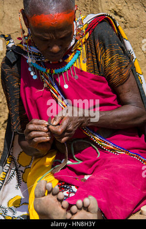 Maasai woman wearing traditional attire weaves beaded jewelry in a village near the Masai Mara, Kenya, East Africa - Stock Photo