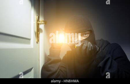 Thief in black bakalave breaks open the door at night - Stock Photo