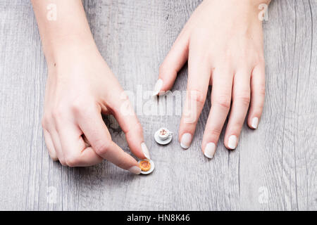 Woman with a minute little model cake and cup of tea moving them with her fingers on a grey rustic table viewed - Stock Photo