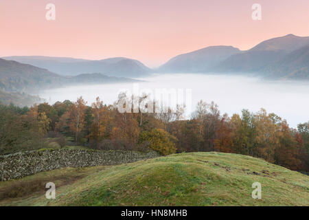 View over Grasmere Lake at sunrise with mist inversion to Heron Pike, Rydal Fell, Great Rigg and Seat Sandal from - Stock Photo