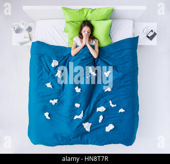 Sad ill woman at home in bed at home surrounded by tissues, she is blowing her nose and sneezing, top view - Stock Photo