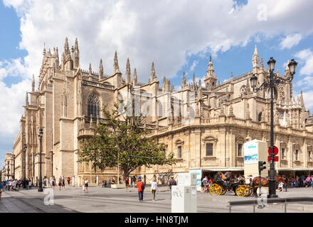 Seville, Spain - April 30, 2016: The Seville Cathedral, view from the south, horse-drawn carriage in front, people - Stock Photo