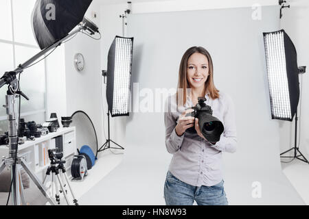 Young female photographer posing in the photo studio, she is smiling and holding a professional digital camera - Stock Photo