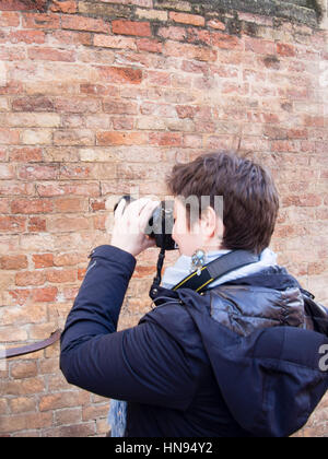 Young woman making photos in the street with Nikon camera - Stock Photo