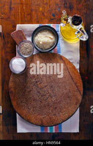 Chopping cutting board on wooden texture background . olive oil, parmesan cheese, pepper, salt. table serving in - Stock Photo