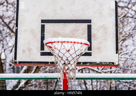 Basketball backboard and red rim or hoop covered with fresh snow, Winter has come. No more outdoor sport activity - Stock Photo