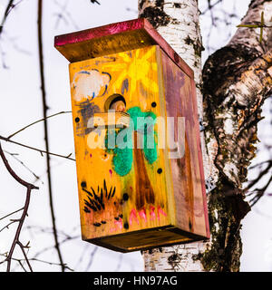 Painted bird nesting box hangs on a birch tree in autumn. Birch tree trunk and branches against the background of - Stock Photo