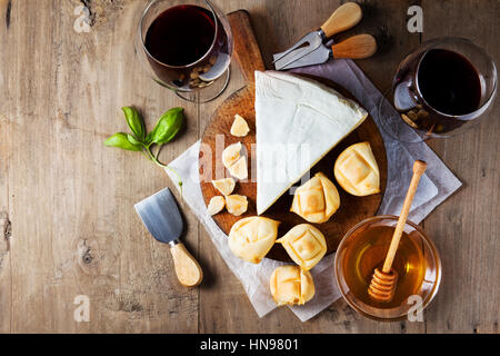 Cheese plate Assortment of various types of cheese and honey on wooden cutting board - Stock Photo