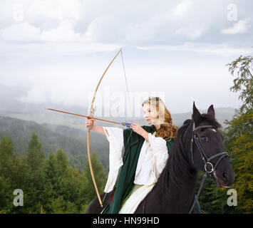 Young horseback girl in white dress shooting arrow from bow in mountain forest. Historical equine background - Stock Photo