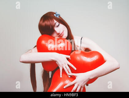 Really happy redhead woman holding red heart shape balloons - Stock Photo