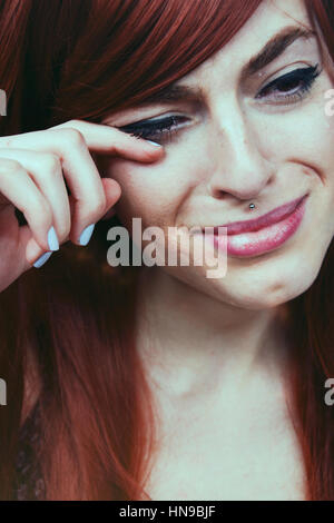 Young redhead woman crying - Stock Photo
