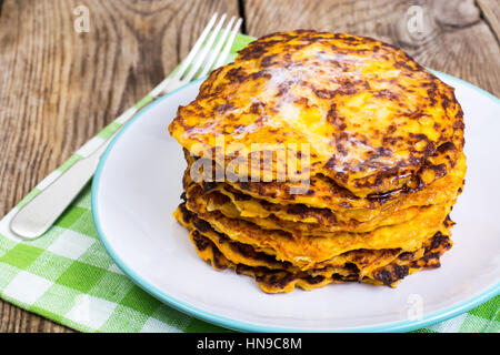 Pumpkin Pancake on plate on background of old wooden planks - Stock Photo