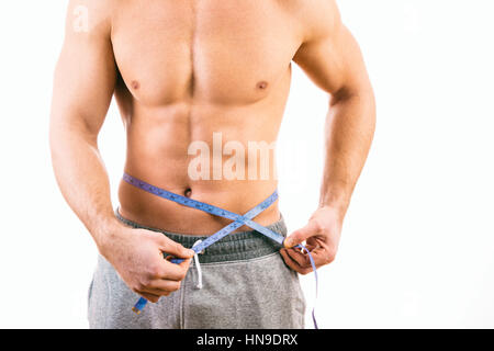 Male torso and blue tape measure on white background - Stock Photo
