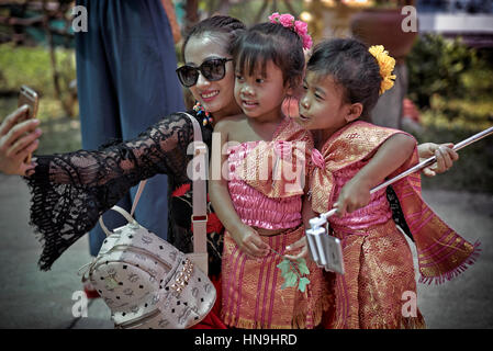 Asian selfie.Chinese tourist woman using a smartphone and taking a selfie photograph with two young 6 year old Thai - Stock Photo