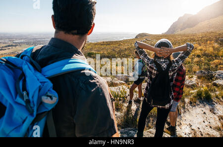 Rear view shot of young people walking in countryside. Group of friends hiking in nature. - Stock Photo
