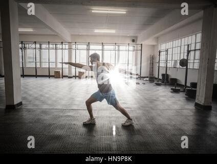 Digital composite of Man stretching in gym with flare - Stock Photo