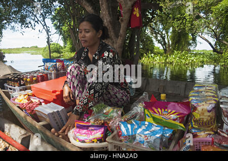 Woman selling confectionary items on boat on floating market. Floating village of Kampong Phluk. Sem Reap Province - Stock Photo