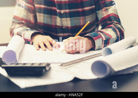 construction engineer working on blueprint at his workplace in office - Stock Photo