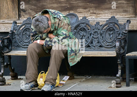 An anonymous  middle aged man - possibly a veteran - sitting with anguished body language on a bench in NOLITA, - Stock Photo