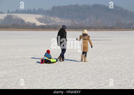 A small family  on a Sunday stroll on  the frozen lake Wallersee in Seekirchen. Salzburger Land, Austria, Europe. - Stock Photo