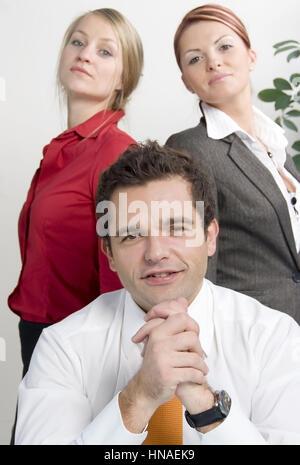 Junger geschaeftsmann mit zwei huebschen Sekretaerinnen - young business man with two attractive secretaries - Stock Photo