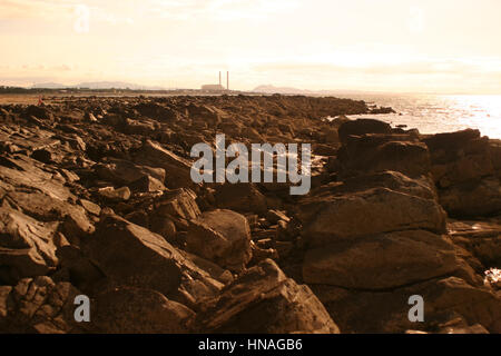 The rocky beach at Longniddry Bents with Cockenzie power station in the background near Edinburgh - Stock Photo