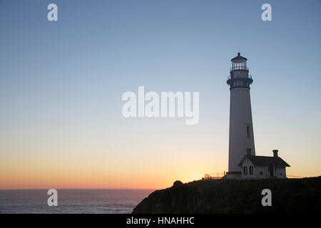 Historic lighthouse on a hill top on the coast of Northern California at Sunset, sun setting behind the light house - Stock Photo