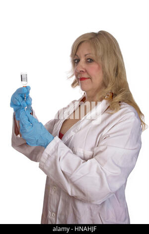 female doctor or nurse with gloved hands in a white lab coat drawing up medication from a vial with a 40 unit per - Stock Photo