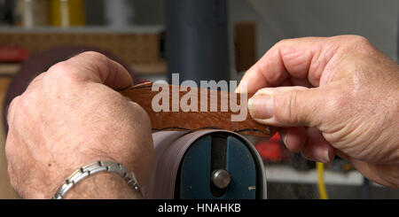 Male hands holding a small piece of cut wood to a table mounted belt sander to smooth the edges on a wood working - Stock Photo