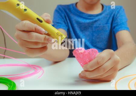Kid hand holding yellow 3D printing pen with filaments and makes heart on white background. Top view. Copy space - Stock Photo