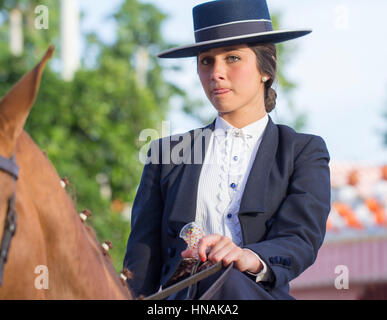 SEVILLE, SPAIN - APR, 25: woman in traditional costume riding horse at the Seville's April Fair on April, 25, 2014 - Stock Photo
