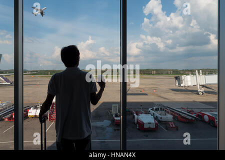 Back side of traveler boy in termainal at airport looking at the flying plane above airport, travel and vacation - Stock Photo