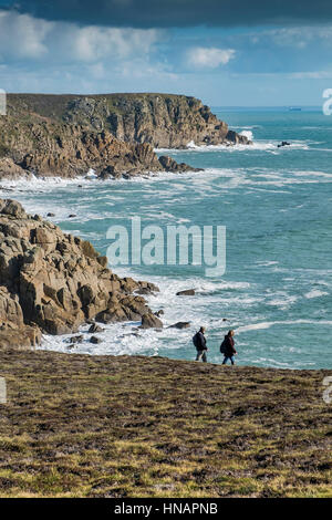 Two walkers on the South West Coastal Path on Gwennap Head in Cornwall, England. - Stock Photo