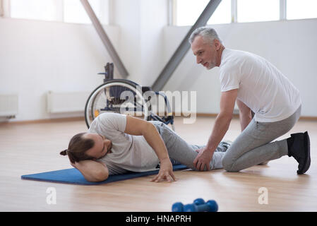 Mindful physical therapist stretching the disabled man in the gym - Stock Photo
