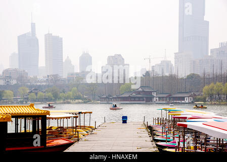 boats on Xuanwu Lake with buildings and Nanjing wall in the background - Stock Photo