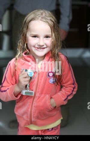 Little girl child kid looking happy and delighted with her winning swimming trophy after swim meet, first place - Stock Photo